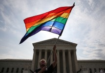 A man holds a six-striped rainbow flag in front of the US Supreme Court.